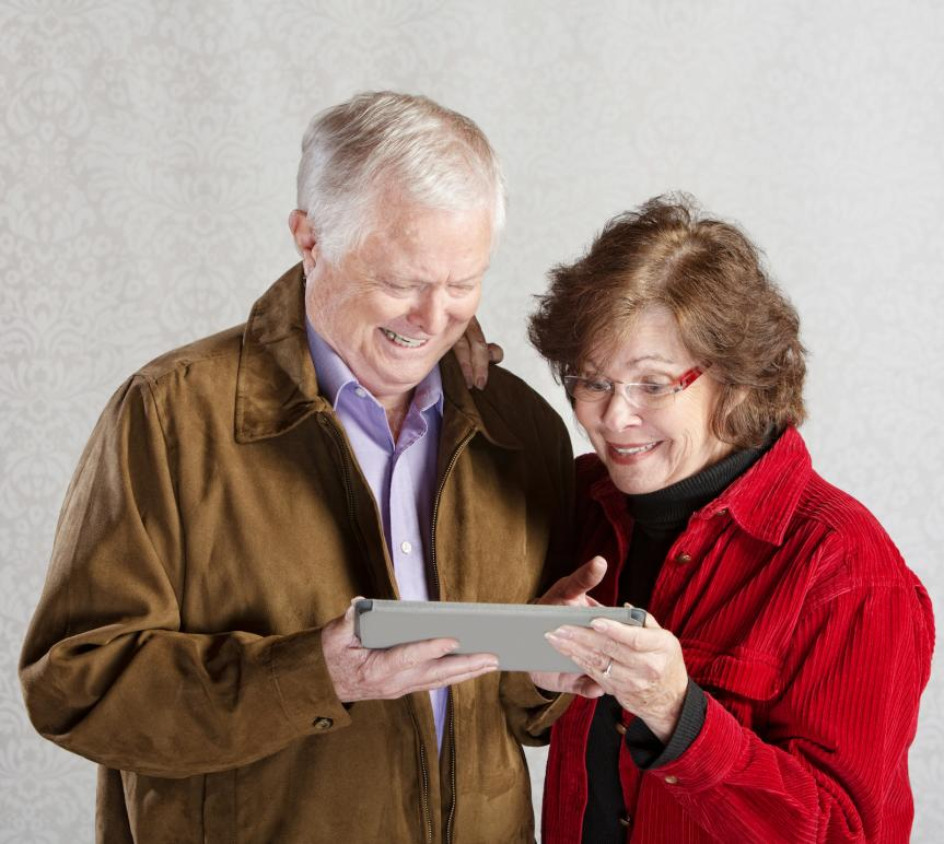 older excited couple with tablet