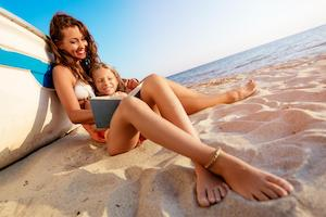 Mother reading to daughter on beach