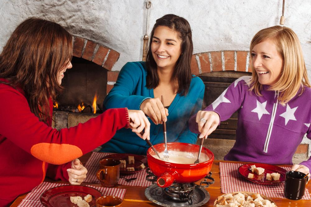Young women eating cheese fondue