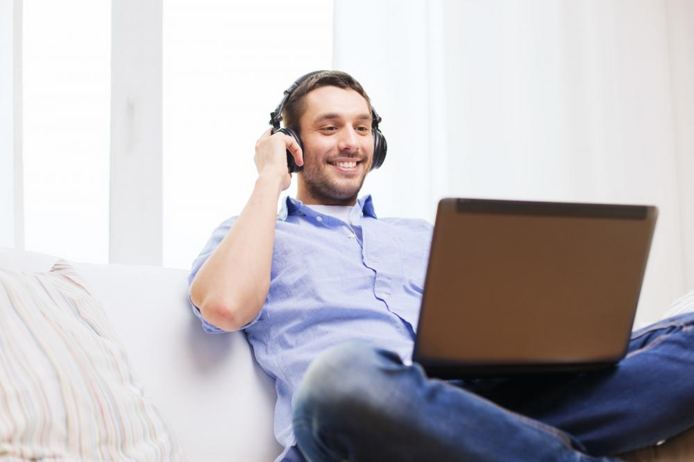 smiling-man-with-laptop-and-headphones-at-home