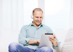 smiling man with tablet and earphone