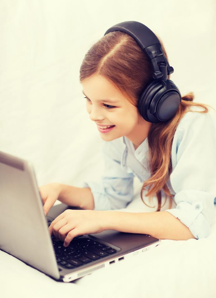 smiling girl on laptop with earphones